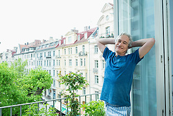 Portrait of mature man standing on balcony, smiling