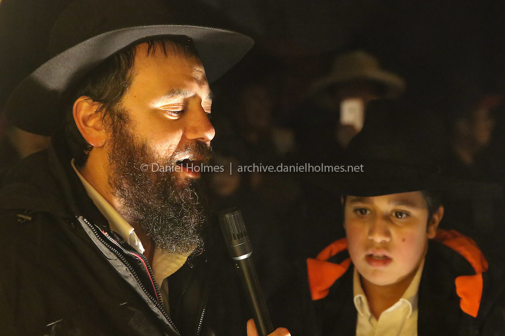 (12/2/18, FRANKLIN, MA) Chabad Rabbi Mendy Kivman sings with his son Shmuly during a celebration of the first night of Hanukkah on the Franklin Town Common on Sunday. [Daily News and Wicked Local Photo/Dan Holmes]
