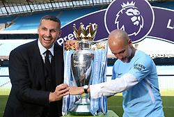 Manchester City manager Pep Guardiola celebrates with chairman Khaldoon Al Mubarak (left) and the Premier League trophy after the Premier League match at the Etihad Stadium, Manchester.