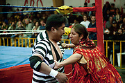 Alicia Flores female wrestler pulling open male opponents shirt out of ring. Lucha Libre wrestling origniated in Mexico, but is popular in other latin Amercian countries, including in La Paz / El Alto, Bolivia. Male and female fighters participate in the theatrical staged fights to an adoring crowd of locals and foreigners alike.