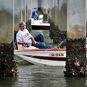 Fishermen duck out from the rain under the William Hilton Parkway bridge next to the C.C. Haigh, Jr. Boat Landing on Pinckney Island during a rainstorm on June 8, 2014.