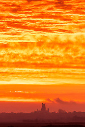 © Licensed to London News Pictures. 23/02/2021. Ely UK. The sky glows bright orange at dawn this morning over Ely Cathedral in Cambridgeshire. Photo credit: Andrew McCaren/LNP