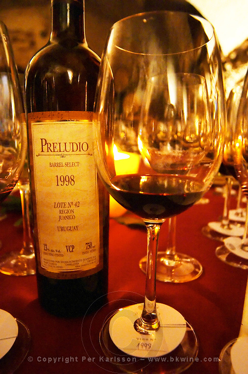 A bottle of Preludio Barrel Select 1998 Lote Number 42 Region Juanico and a glass of the same wine at dining and tasting table filled with glasses. Bodega Juanico Familia Deicas Winery, Juanico, Canelones, Uruguay, South America