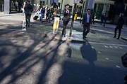 City businessmen cross the road where reflected light from a nearby banking institution, on 27th October 2017, in the City of London, England.