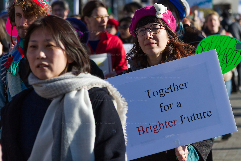A woman holds a sign saying Together for a Brighter Future at a protest march and rally organised by the Alliance for an Inclusive America group against the perceived anti-Muslim and anti-foreigner immigration policies of President Donald Trump, Shibuya, Tokyo, Japan. Sunday February 12th 2017. The Alliance of an Inclusive America is a multi-faith non-partisan group. About 250 Americans, other ex-pats and japanese people took part in the march to show people around the world they reject the Executive Order President Trump enacted at the end of January, indefinitely suspending the resettlement of Syrian refugees and temporarily banning people from seven majority Muslim countries from entering the United States.