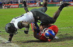 Nov 28, 2009; Kansas City, MO, USA; Kansas wide receiver Kerry Meier (10) makes the catch for a touchdown as Missouri safety Jarrell Harrison (11) attempts the tackle in the fourth quarter at Arrowhead Stadium.The Tigers won 41-39.Mandatory Credit: Denny Medley-US PRESSWIRE