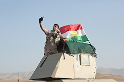 20/10/2016. Bashiqa, Iraq. A Kurdish peshmerga machine gunner takes a selfie with the Kurdish flag on the turret of his armoured Humvee as he takes part in a large offensive to retake the Bashiqa area from Islamic State militants today (20/10/2016).<br /> <br /> Launched in the early hours of today with support from coalition special forces and air strikes, the attack is part of the larger operation to retake Mosul from the Islamic State, and involves both the Kurds and the Iraqi Army. The city of Bashiqa, around 9 miles north of Mosul, is one of several gateway areas that must be taken before any attempted offensive on Mosul itself.<br /> <br /> Despite the peshmerga suffering several casualties after militants fought back using mortars, heavy machine guns and snipers, the Kurdish forces were quickly taking ground with Haider al-Abadi, the Iraqi prime minister, stating that the operation to retake Mosul was progressing faster than expected. Photo credit: Matt Cetti-Roberts/LNP
