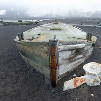 Decaying whaling boats lay next to a whale bone at Whaler's Bay on Deception Island, Antarctica.