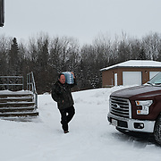 Aaron Henry, Water Plant Operator at the Ochiichagwe'Babigo'Ining Ojibway Nation reserve (also known as the Dalles First Nation) in Northern Ontario, Canada, leaving the plant to visit a resident whose water had stopped flowing on 19 December 2016. He delivered the water he is carrying to ensure that the household had potable water while the problem was resolved. The water treatment plant is participating in a pilot program which will see water quality monitored in real time via an Internet link to a central Water Hub at the Bimose Tribal Council in the town of Kenora, about 30 minutes drive away.