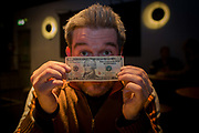 English author, Steve Boggan with the $10 note that he shadowed across America, described in his book 'Follow the Money'. Boggan is a journalist for UK newspapers and magazines and so by setting free a ten-dollar bill and accompanying it on an epic journey for thirty days and thirty nights across 3,300 miles armed only with a sense of humour and a small, and increasingly grubby, set of clothes. He wrote his book in order to trace the life of the bill - but also to discover something of the lives of modern Americans in an age when plastic cards have largely overtaken the use of paper money in everyday use, especially in small town America.