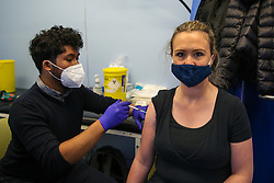 © Licensed to London News Pictures. 20/05/2021. London, UK. Aaron Rahman, Covid-19 vaccinator administers the Pfizer and BioNTech vaccine to a woman at a vaccination centre in Haringey, north London. According to government figures, more than 70% of UK adults have received their first dose of a COVID-19 vaccine and nearly 40% of have been both doses. People aged between 34-35 years olds are now been invited for their Covid-19 vaccine.<br /> <br /> ***Permission Granted*** <br /> <br /> Photo credit: Dinendra Haria/LNP
