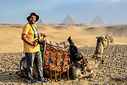 Mohamed and his camel taking a break in the desert with the Pyramids of Giza in the background