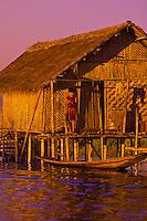 Girl standing outside house on stilts, Nampan, Inle Lake, Myanmar (Burma)