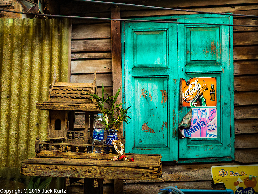 25 SEPTEMBER 2016 - BANGKOK, THAILAND: An antique wooden spirit house in front of a home in the Pom Mahakan community. Forty-four families still live in the Pom Mahakan Fort community. The city of Bangkok has given them provisional permission to stay, but city officials say the permission could be rescinded and the city go ahead with the evictions. The residents of the historic fort have barricaded most of the gates into the fort and are joined every day by community activists from around Bangkok who support their efforts to stay.      PHOTO BY JACK KURTZ