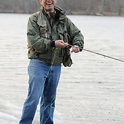 "Fly fishing coach Macauley Lord takes a break from teaching to smile at the camera on the banks of the Androscoggin River on Thursday afternoon. Lord, who is studying ministry at Bangor Theological Seminary says, ""chaplaincy is more like coaching than fishing.""  He started coaching in 1986 -- but has fished since '68. Photo by Roger S. Duncan."
