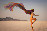 Nude woman dancing and waving a long scarf at the Bonneville Salt Flats, Utah