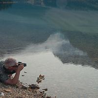 A photographer frames a scene beside Bow Lake in Banff National Park, Alberta, Canada.