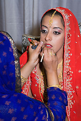 Bride in traditional Asian dress being made up before her wedding,