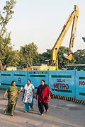 Women walk past a construction site near Hauz Khas, New Delhi, India