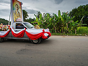 31 AUGUST 2014 - SARIKA, NAKHON NAYOK, THAILAND: A truck carrying carrying a portrait of Bhumibol Adulyadej, the King of Thailand, leads the way to a river where statues of Ganesh will be submerged at Shri Utthayan Ganesha Temple in Sarika, Nakhon Nayok. Ganesh Chaturthi, also known as Vinayaka Chaturthi, is a Hindu festival dedicated to Lord Ganesh. It is a 10-day festival marking the birthday of Ganesh, who is widely worshiped for his auspicious beginnings. Ganesh is the patron of arts and sciences, the deity of intellect and wisdom -- identified by his elephant head. The holiday is celebrated for 10 days, in 2014, most Hindu temples will submerge their Ganesh shrines and deities on September 7. Wat Utthaya Ganesh in Nakhon Nayok province, is a Buddhist temple that venerates Ganesh, who is popular with Thai Buddhists. The temple draws both Buddhists and Hindus and celebrates the Ganesh holiday a week ahead of most other places.    PHOTO BY JACK KURTZ