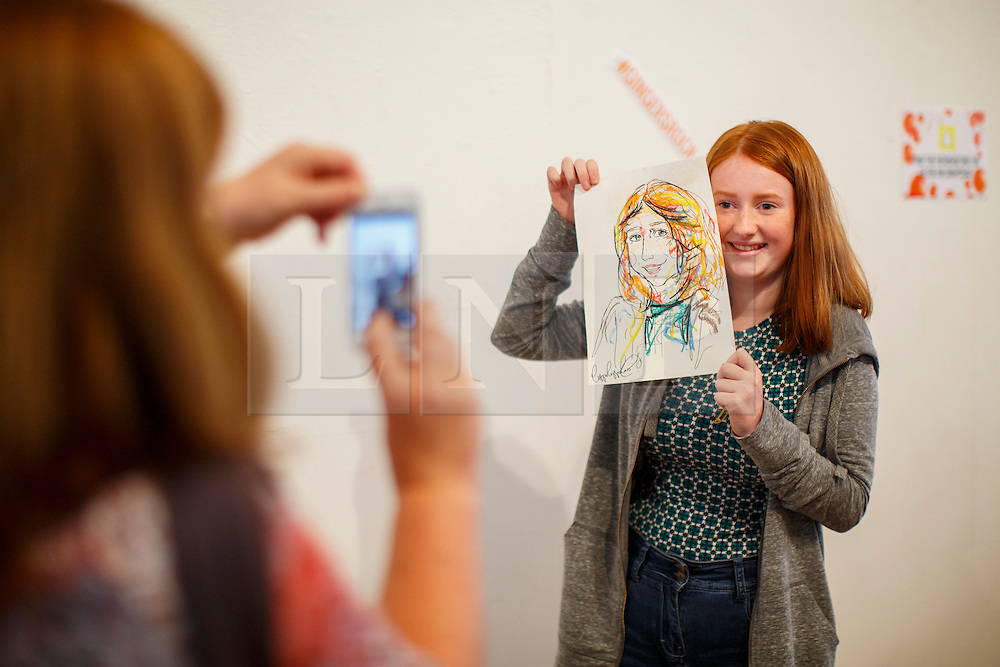 © Licensed to London News Pictures. 17/09/2016. London, UK. Emily Johnson poses with a hand drawn portrait of her as hundreds of redheads attend Redhead Day UK event in Angel, London on Saturday, 17 September 2016. Natural redhead visitors get chance to celebrate their ginger genes and shop specialised products, see ginger related exhibitions and live performances. Photo credit: Tolga Akmen/LNP