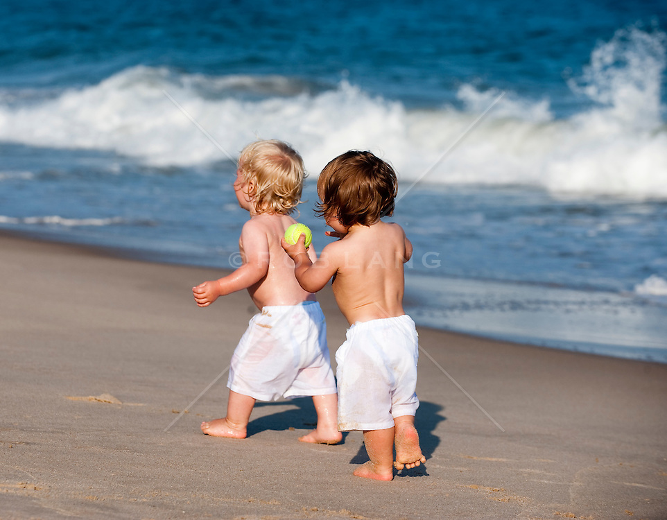 Two little boys walking by the shore in East Hampton, NY