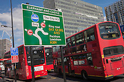 London buses and a traffic sign showing the new road layout at Elephant & Castle, south London.