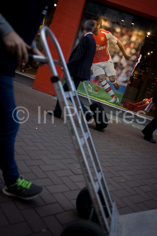 Diagonal angle of Arsenal footballer and trolley, in Carnaby Street, London. In a coincidence of diagonal slants, we see the Arsenal footballer Mathieu Flamini on the field during a football game. His image appears in the shop window of sports brand Puma. Sharing the slant are a man pulling his luggage and a delivery man who pushes an empty trolley in front of him, the diagonals matching the scene.