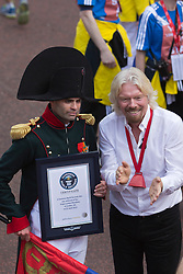 © Licensed to London News Pictures. 21/04/2013. London, England. Sir Richard Branson poses with a Runner attempting a Guinness World Record. Celebrity Runners and Fun Runners finish the Virgin London Marathon 2013 race in the Mall, London. Many wore black ribbons to pay their respect for those who died or were injured in the Boston Marathon. Photo credit: Bettina Strenske/LNP