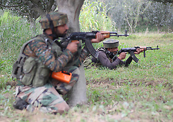 August 26, 2017 - India - Indian army men take position in an apple orchard near the site of gunbattle after militants stormed the District police lines (DPL) complex in Pulwama some 30 kilometers south of Srinagar the summer capital of Indian controlled Kashmir on August 26, 2017.Two paramilitary soldiers and one policeman of Special Operation Group (SOG) were killed in an ongoing gunbattle ,Police reported (Credit Image: © Faisal Khan/Pacific Press via ZUMA Wire)