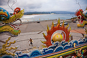 A man with a surfboard walks by the temple facing Nuclear Power Plant Number 4 in Fulong, Taiwan, decorated with dragons and other images from ancient Chinese mythology.