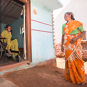 CAPTION: Rajamma, who has severe rheumatoid arthritis, gets around her home by crawling. She has a new wheelchair, but her mother Mahadevamma will not be able to wheel her into and out of her house in this until construction of the ramp up to the doorway has been completed. LOCATION: Amchawadi (village), Haradanahalli (hobli), Chamrajnagar (district), Karnataka (state), India. INDIVIDUAL(S) PHOTOGRAPHED: Rajamma (left) and Mahadevamma (right).