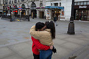 As the Coronavirus pandemic spreads across the UK, businesses and entertainment venues not already closed with the threat of job losses, struggle to stay open with growing rumours of a lockdown and travel restrictions around the capital. As Londoners start to work from home, observing government advice for social distancing, Brazilian waiter Luis and his au pair girlfriend, Paula from Spain, kiss and hug in an unusually quiet Piccadilly Circus, on 19th March 2020, in London, England.