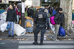 PARIS, Oct. 31, 2016 (Xinhua) -- A policeman stands in front of migrants during a police operation aiming at a future evacuation of a refugee camp in Paris, France, on Oct. 31, 2016. French Police on Monday checked identities of thousands of migrants camping outside Stalingrad Metro Station, north Paris to prepare the camp's evacuation, local media reported. (Xinhua/John Fiddler) (dtf) (Credit Image: © John Fiddler/Xinhua via ZUMA Wire)