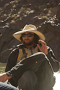Rico Alderete holds court while on his motor raft, Colorado River, Grand Canyon National Park; model release on file