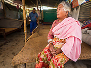 04 AUGUST 2015 - BUNGAMATI, NEPAL:  A woman sits on her bed in the temporary structure she shares with eight other families in Bungamati, a village about an hour from Kathmandu. Three months after the earthquake many families still live in tents and temporary shelters scattered around the village. The Nepal Earthquake on April 25, 2015, (also known as the Gorkha earthquake) killed more than 9,000 people and injured more than 23,000. It had a magnitude of 7.8. The epicenter was east of the district of Lamjung, and its hypocenter was at a depth of approximately 15 km (9.3 mi). It was the worst natural disaster to strike Nepal since the 1934 Nepal–Bihar earthquake. The earthquake triggered an avalanche on Mount Everest, killing at least 19. The earthquake also set off an avalanche in the Langtang valley, where 250 people were reported missing. Hundreds of thousands of people were made homeless with entire villages flattened across many districts of the country. Centuries-old buildings were destroyed at UNESCO World Heritage sites in the Kathmandu Valley, including some at the Kathmandu Durbar Square, the Patan Durbar Squar, the Bhaktapur Durbar Square, the Changu Narayan Temple and the Swayambhunath Stupa. Geophysicists and other experts had warned for decades that Nepal was vulnerable to a deadly earthquake, particularly because of its geology, urbanization, and architecture.    PHOTO BY JACK KURTZ