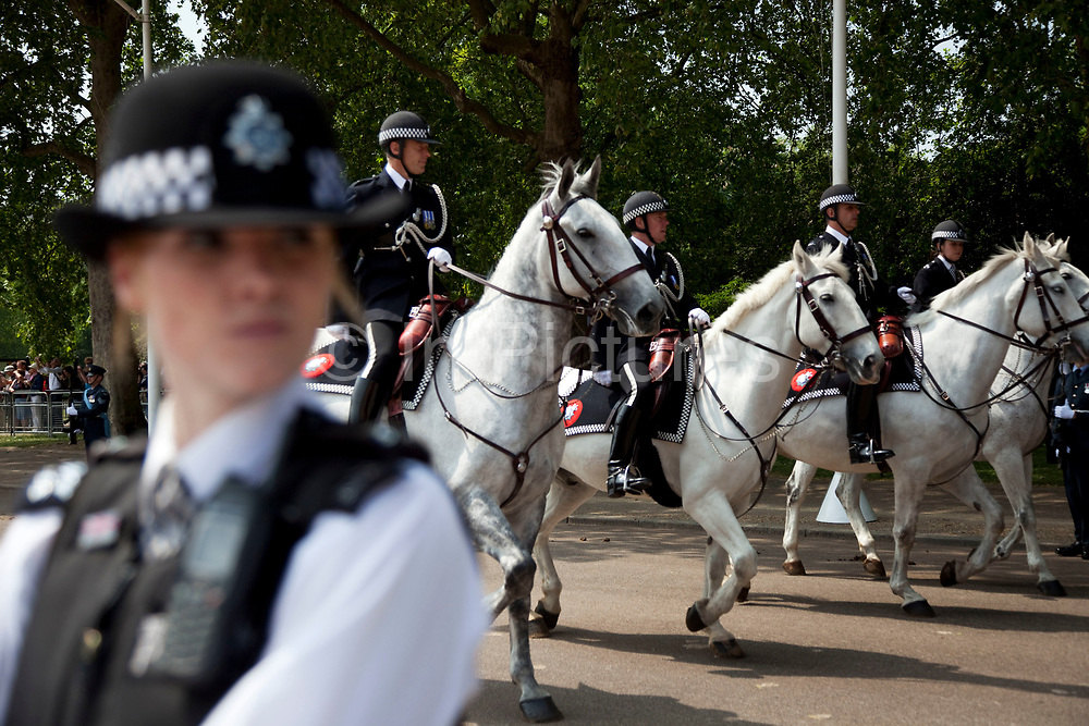 Royal procession for the State Opening of Parliament, London. Mounted police pass a WPC on duty.