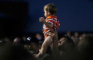 A man seated in the section reserved for immediate family of the 19 firefighters killed in a nearby wildfire holds up a baby toward the audience in Prescott, Arizona July 2, 2013. REUTERS/Rick Wilking (UNITED STATES)