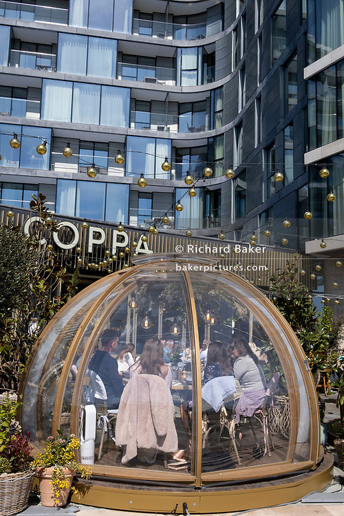 As Covid lockdown restrictions continue to ease and non-essential businsses re-open, customers enjoy al fresco dining at 'Coppa Club', a riverside restaurant located beneath luxury apartments near the Tower Of London, on 26th April 2021, in London, England. 'Coppa Club' is part of the Strada-branded restaurant chain specialising in Italian cuisine.