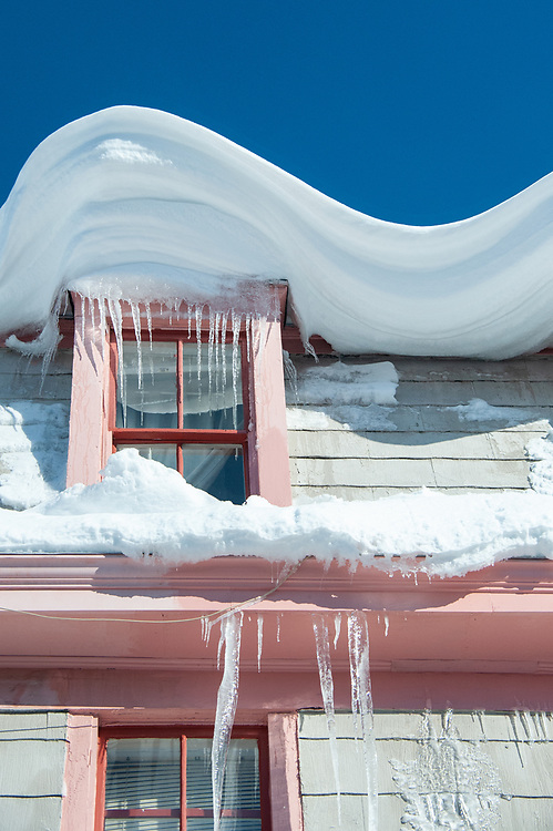 Snow swirled on roof dripping with icecicles.