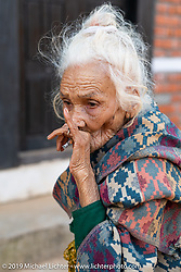 Old woman smoking in Nuwakot during Motorcycle Sherpa's Ride to the Heavens motorcycle adventure in the Himalayas of Nepal. This first day of riding took us from Kathmandu to Nuwakot. Monday, November 4, 2019. Photography ©2019 Michael Lichter.