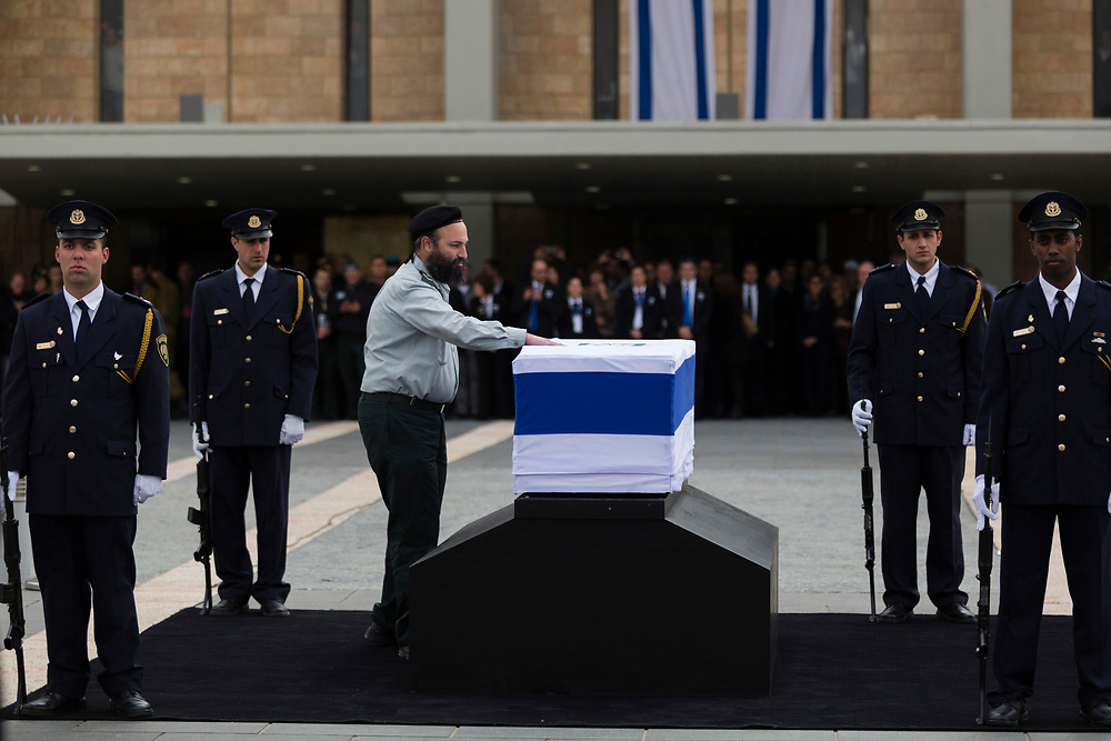 An Israeli army rabbi touches the coffin of former Israeli Prime Minister Ariel Sharon, as it lies in state at the Knesset, Israel's parliament in Jerusalem, on January 12, 2014. Sharon, a former Israeli general and prime minister, died Saturday, aged 85, after eight years in a coma caused by a stroke.