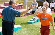 Happy medal winner high fiving policeman. Special Olympics U of M Bierman Athletic Complex. Minneapolis Minnesota USA
