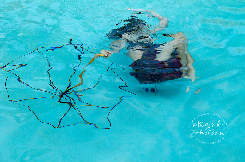 Teenage girl with umbrella underwater in swimming pool ****Model Release available