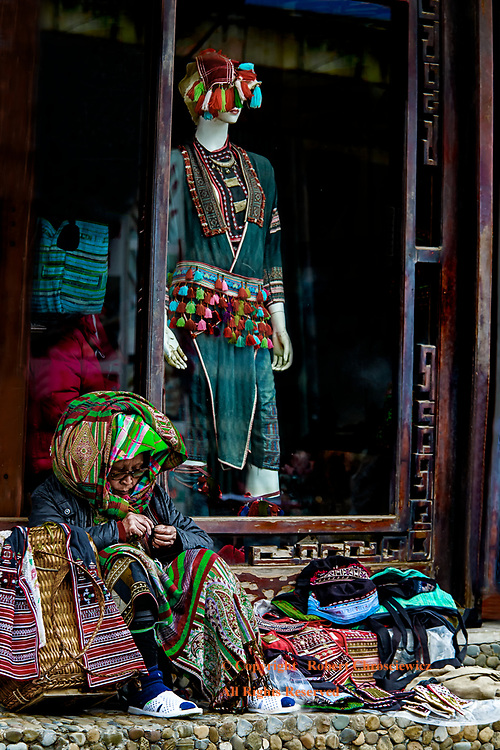 Competition: A woman sews her own tribal offerings in direct competition to a fashionable store that sells idealized local women's wear to foreigners, Sapa Vietnam.