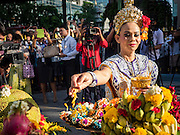 "04 SEPTEMBER 2015 - BANGKOK, THAILAND:  A Thai dancer makes an offering durinf a blessing ceremony at the Erawan Shrine Friday. A ""Holy Religious Ceremony for Wellness and Prosperity of our Nation and Thai People"" was held Friday morning at Erawan Shrine. The ceremony was to regain confidence of the Thai people and foreign visitors, to preserve Thai religious customs and traditions and to promote peace and happiness inThailand. Repairs to Erawan Shrine were completed Thursday, Sept 3 after the shrine was bombed on August 17. Twenty people were killed in the bombing and more than 100 injured. The statue of the Four Faced Brahma in the shrine was damaged by shrapnel and a building at the shrine was damaged by debris.    PHOTO BY JACK KURTZ"