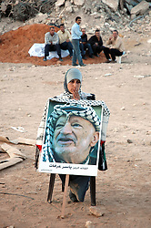 © London News Pictures. FILE PIC DATED 12/11/2004. Ramallah, West Bank.  A woman holding a poster showing the face of Yasser Arafat at the grave of Yasser Arafat after he was buried in the compound of the Muqaata in the West Bank city of Ramallah.  Scientists are due to exhume the remains of Yasser Arafat in an effort to determine whether his death in 2004 was caused by polonium-210 poisoning.   Photo credit: Grant Fleming/LNP