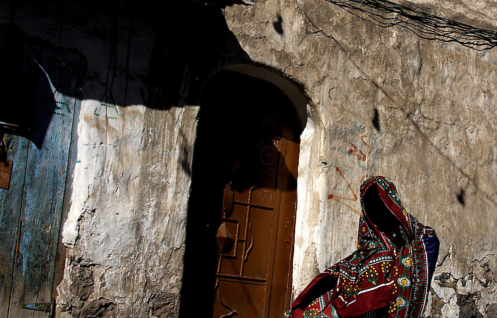"""San'a, the old city of the Yemen capital made up of alleys and souqs has been declared among the UNESCO protected sites.<br /> In this country women are always covered sometimes even with gloves and veils on the face so that no skin lobster leaks out. In Sura 24 verse 31, that is in a passage, the Koran reads: """"Women cover both breasts with veils of their heads, they do not display female ornaments except their husbands"""" and a circle of family members. In Sura 33 in verse 59 we read: """"O prophet, tell your brides and daughters and the women of believers to cover themselves with their cloaks; they will allow them to be distinguished from other women and to ensure that they are not offended"""". .. In some countries the Koran is followed with extreme rigor, and the women who transgress risk sentences and penalties<br /> <br /> Yemen, January 2006 <br /> <br /> Photo Antonietta Baldassarre Insidefoto(www.insidefoto.com)"""