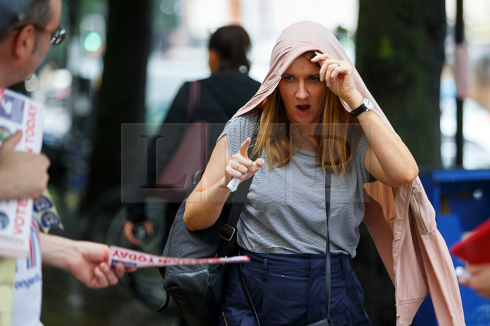 © Licensed to London News Pictures. 23/06/2016. London, UK. A woman is being offered a Stronger In referendum leaflet whilst running to take shelter in the rain in Islington, London on the polling day of the EU referendum on 23 June 2016. Photo credit: Tolga Akmen/LNP