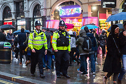 London, December 31 2017. The umbrellas come out as a downpour begins in London's west end ahead of the New Year's Eve fireworks at midnight. PICTURED: Police officers walk through the rain near Leicester Square. © SWNS